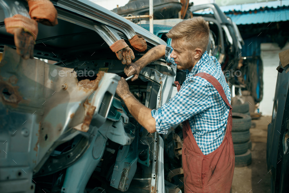 Male repairman poses on car junkyard - Stock Photo - Images