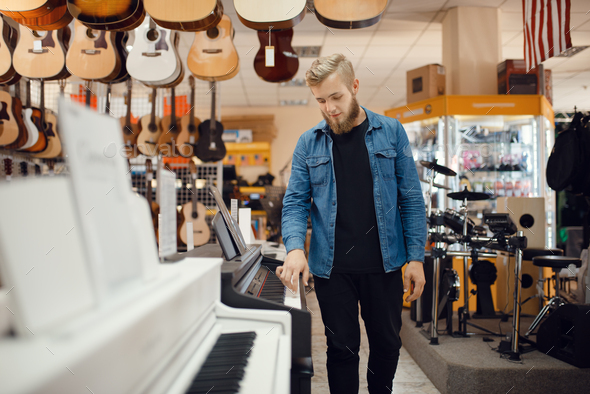 Young musician poses at the piano in music store - Stock Photo - Images