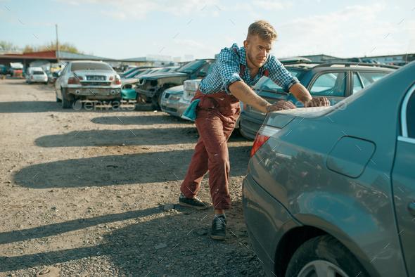 Male mechanic pushing the car on junkyard - Stock Photo - Images