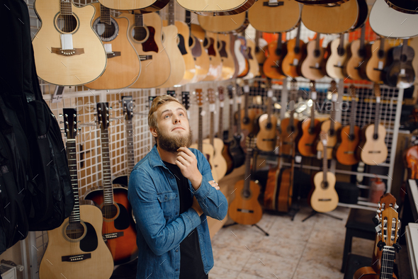 Young guy choosing acoustic guitar in music store - Stock Photo - Images