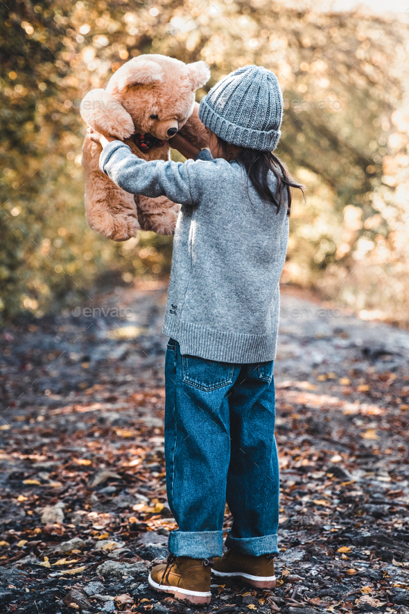 Little girl holds a bear in her arms on the background of nature on an autumn day - Stock Photo - Images