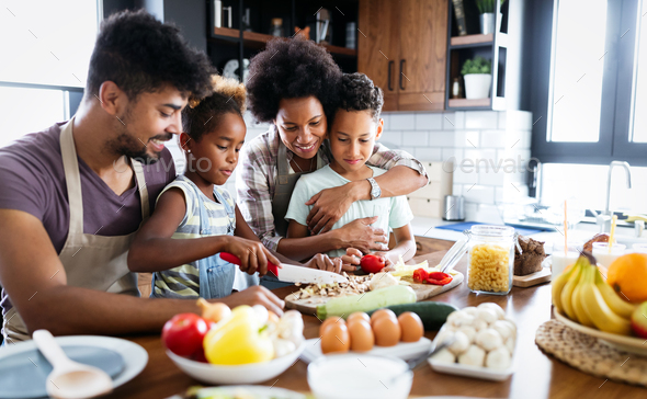 Happy family in the kitchen having fun and cooking together. Healthy food at home - Stock Photo - Images