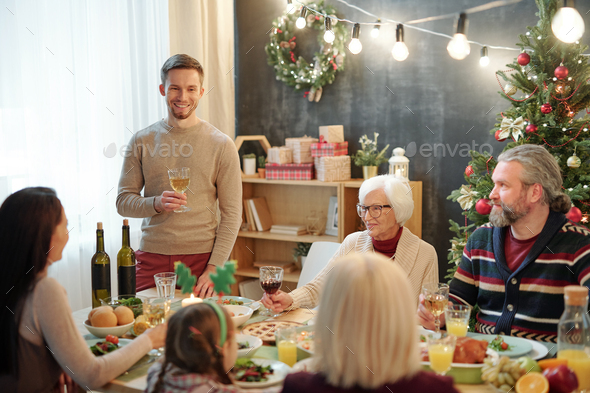 Cheerful man with glass of wine toasting by served table in front of his family - Stock Photo - Images