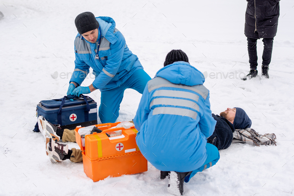 Two paramedics in uniform giving first aid to sick unconscious man lying on snow - Stock Photo - Images