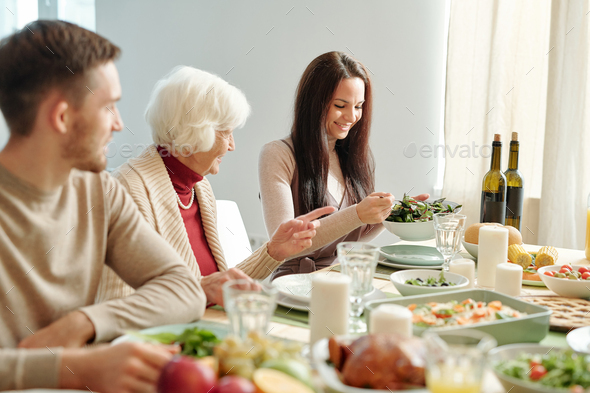 Happy young brunette woman putting salad on plate of grandma by dinner - Stock Photo - Images
