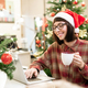 Cheerful young office worker in Santa cap having cup of tea in front of laptop - PhotoDune Item for Sale