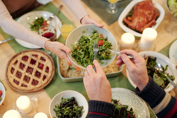 Top view of hands of man taking salad from plate held by young woman - Stock Photo - Images