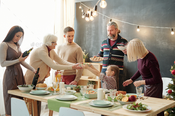 Cute little girl passing bowl with salad to her great grandma by festive table - Stock Photo - Images