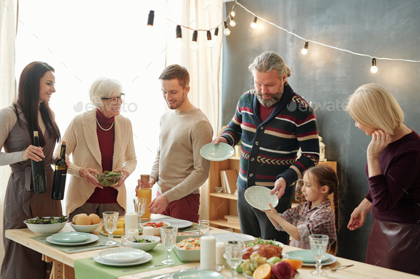 Family of five taking plates for snacks and preparing drinks before celebration - Stock Photo - Images
