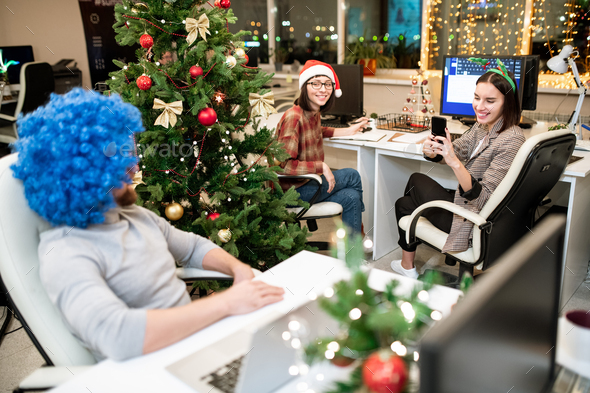 One of young happy businesswomen taking photo of colleague in blue wig - Stock Photo - Images