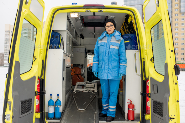Young female paramedic in uniform standing by empty stretcher in ambulance car - Stock Photo - Images