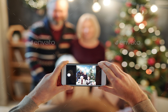 Hands of man holding smartphone while taking photo of big relaxed family - Stock Photo - Images