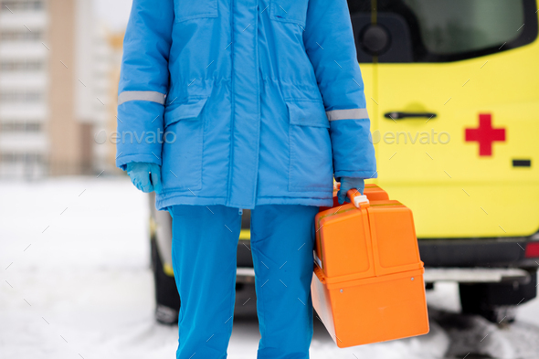 Mid-section of young paramedic in blue workwear and gloves holding first aid kit - Stock Photo - Images
