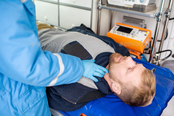 Gloved hand of paramedic cheking pulse of sick man lying on stretcher - Stock Photo - Images
