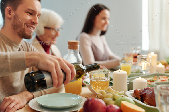 Young man pouring wine into wineglass while sitting by served table - Stock Photo - Images