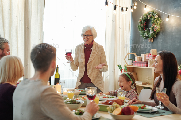 Senior grey-haired female toasting with glass of red wine in front of her family - Stock Photo - Images