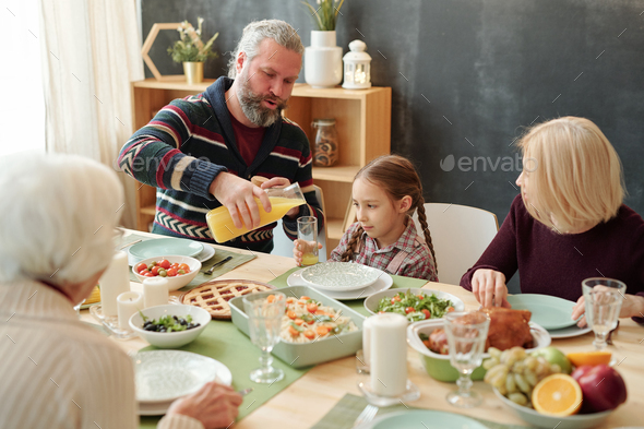 Grandfather pouring fruit juice into glass of his granddaughter by festive table - Stock Photo - Images