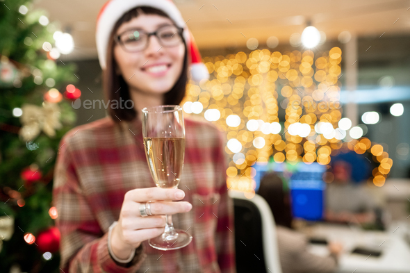 Hand of female office manager holding flute of champagne in front of camera - Stock Photo - Images