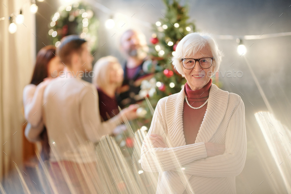 Happy grandma with her arms crossed on chest wishing you merry Christmas - Stock Photo - Images