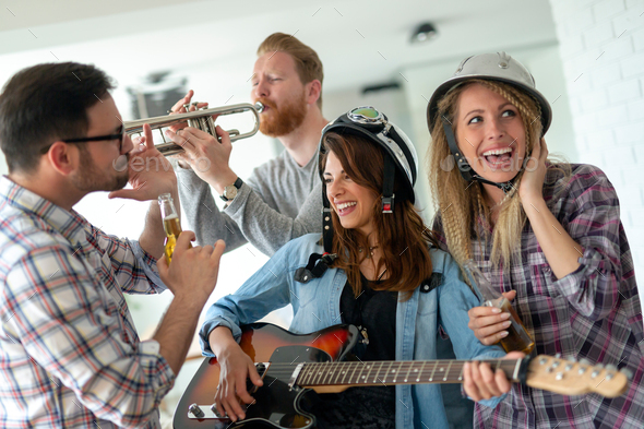 Group of young friends having fun together and playing in music band - Stock Photo - Images