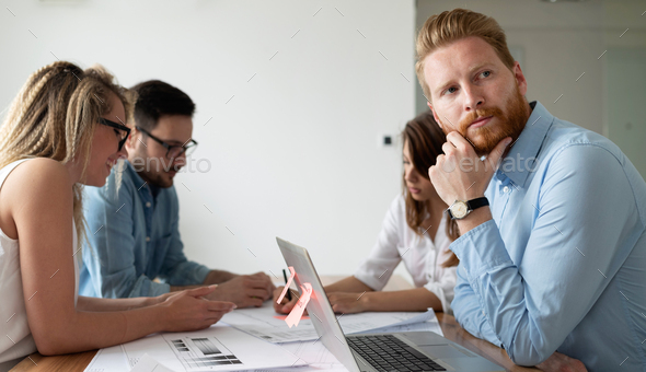 Group of business people working and communicating while sitting at the office desk together - Stock Photo - Images