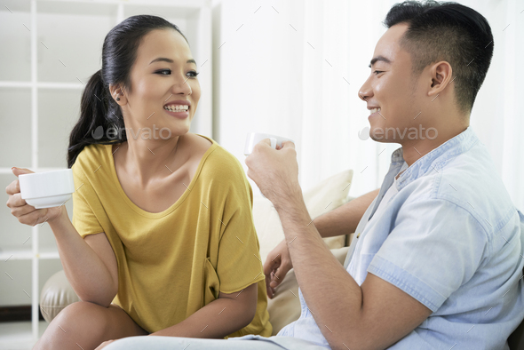 Chilling couple with coffee cups on sofa - Stock Photo - Images