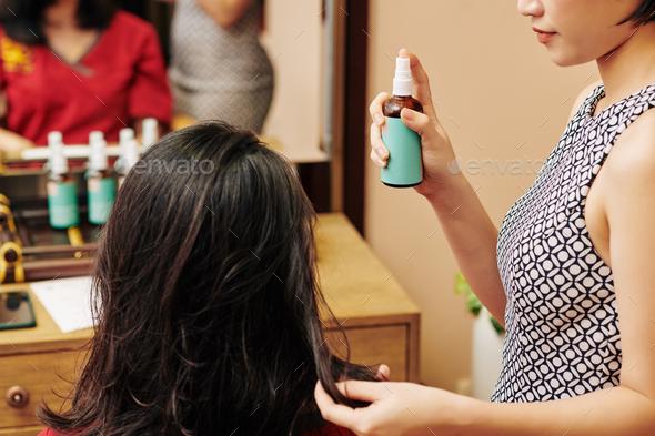 Hairdresser applying moisturizing serum - Stock Photo - Images