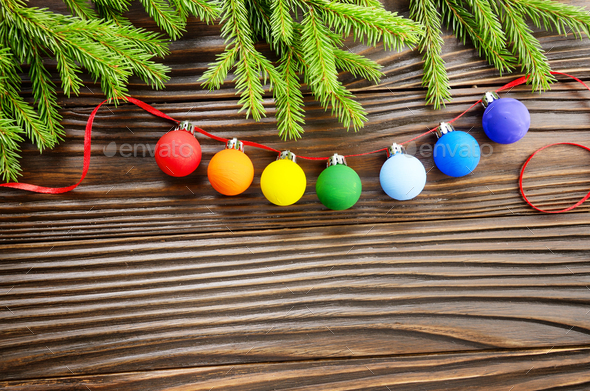 Christmas background of spruce branches and colorful balls on wo - Stock Photo - Images