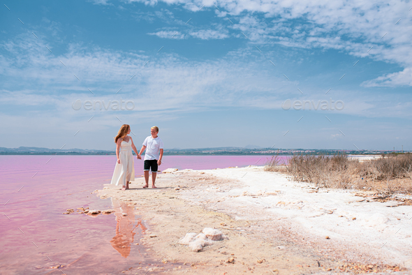 cute teenager couple walking on a shore of amazing pink lake - Stock Photo - Images