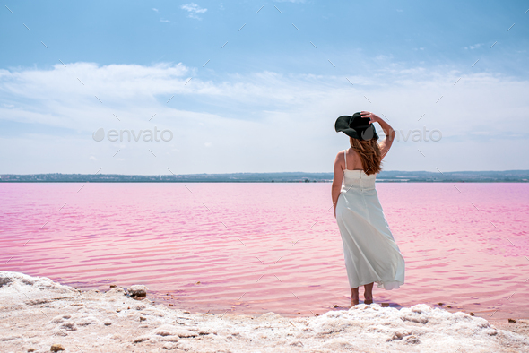 Back view of cute teenager woman wearing white dress walking on a amazing pink lake - Stock Photo - Images