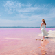 Back view of cute teenager woman wearing white dress walking on a amazing pink lake - PhotoDune Item for Sale