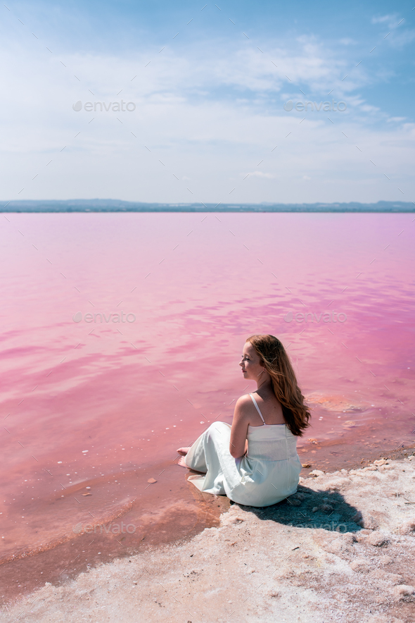cute teenager woman wearing white dress sitting on an amazing pink lake - Stock Photo - Images