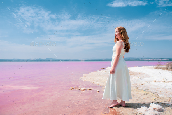 Side view of cute teenager woman wearing summer clothes on pink lake - Stock Photo - Images