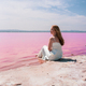 cute teenager woman wearing white dress sitting on an amazing pink lake - PhotoDune Item for Sale