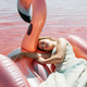 Beautiful woman lying on inflatable float mattress on pink sea - PhotoDune Item for Sale