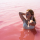 cute teenager girl wearing white dress in the water of an amazing pink lake - PhotoDune Item for Sale