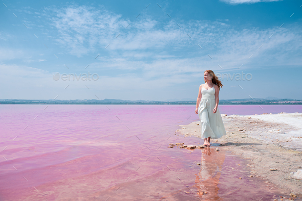 cute teenager woman wearing white dress walking on a amazing pink lake - Stock Photo - Images