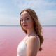 Side view of cute teenager woman wearing summer clothes standing on an amazing pink lake - PhotoDune Item for Sale