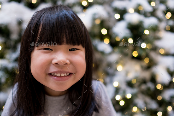Portrait of a happy excited girl with the Christmas tree background - Stock Photo - Images