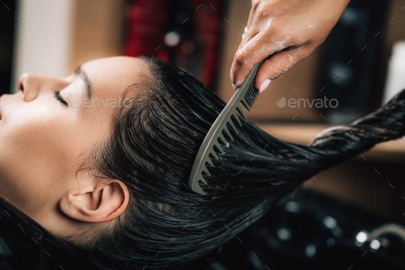 Hairdresser brushing woman's long black hair. - Stock Photo - Images