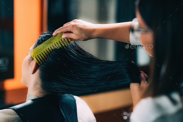 Hairdresser Brushing Woman's Wet Hair - Stock Photo - Images