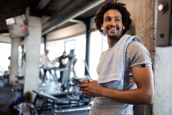 Young handsome man using phone while having exercise break in gym - Stock Photo - Images
