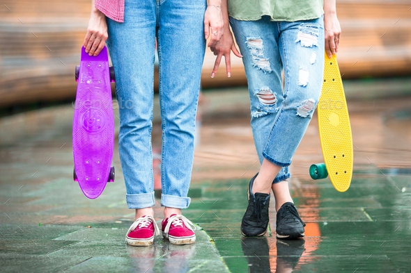 Two hipster urban girls with skateboard outdoors in sunset light. Closeup skatebords in female hands - Stock Photo - Images