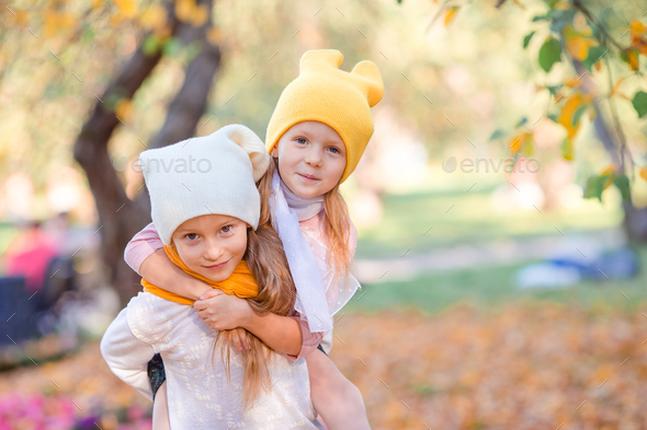 Little adorable girls at warm day in autumn park outdoors - Stock Photo - Images