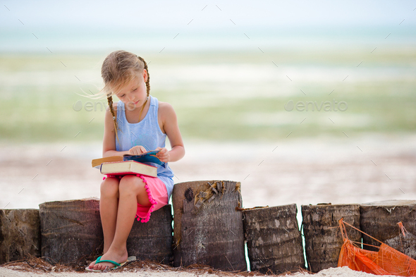 Little adorable girl with book on tropical white beach - Stock Photo - Images