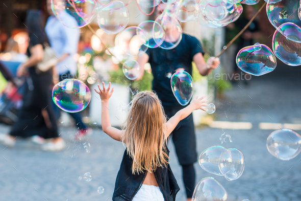 Adorable little girl blowing soap bubbles in Trastevere in Rome, Italy - Stock Photo - Images