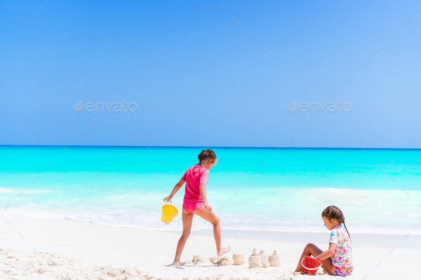 Adorable little girls during summer vacation. Kids playing with beach toys on the white beach - Stock Photo - Images