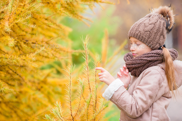 Portrait of adorable little girl with yellow leaves bouquet in fall - Stock Photo - Images