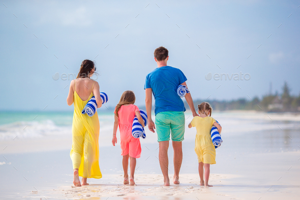 Back view of a young family on tropical beach - Stock Photo - Images