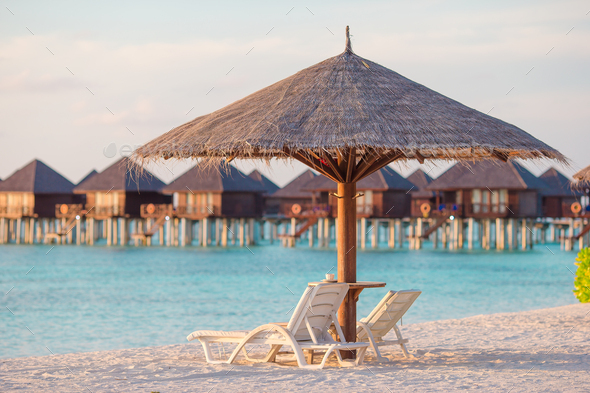 White lounge chairs on a beautiful tropical beach at Maldives - Stock Photo - Images
